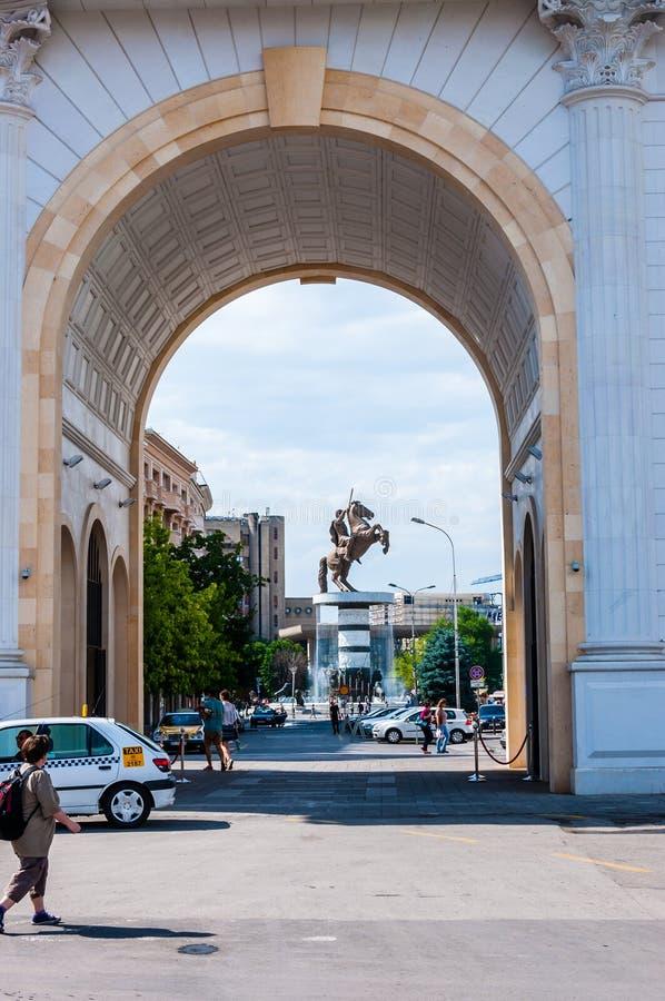 Sikt till och med en berömd triumf- båge Porta Makedonien på en jättebronsstaty av Alexander det stort på den Macedonian fyrkante fotografering för bildbyråer