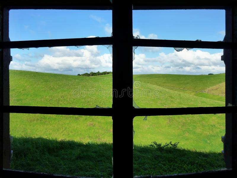 Sikt till och med ett brutet fönster på ängar royaltyfri fotografi