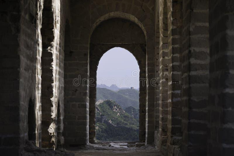 Sikt till och med ett tegelstenfönster av en fästningvakt Tower av Mutianyu, ett avsnitt av den stora väggen av Kina under som arkivfoton