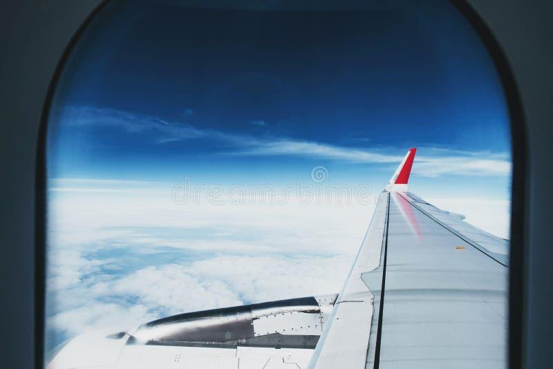 Sikt till och med flygplanfönster den härliga flyg- sikten av blå himmel och vit fördunklar på natten, medan resa fotografering för bildbyråer
