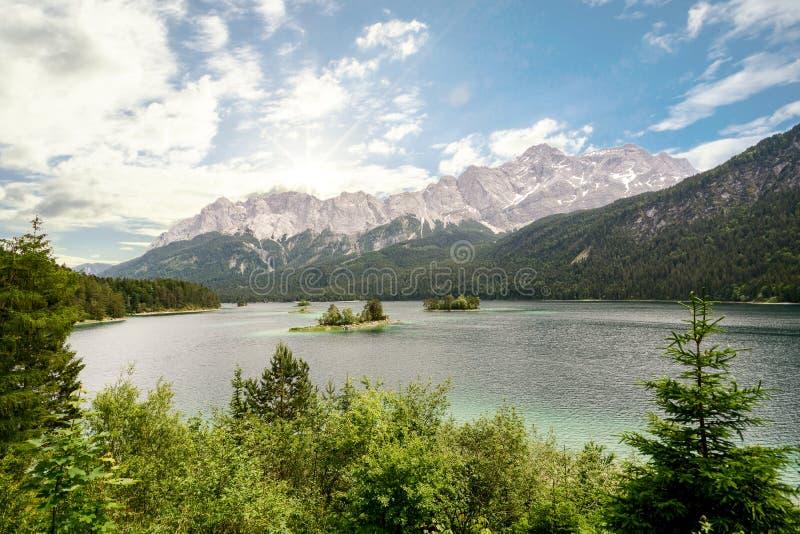 Sikt till sjön Eibsee och Zugspitze, högst berg för Tyskland` s Tyskland i för bavarianfjällängarna, Bayern royaltyfria foton