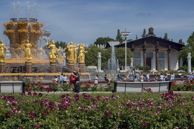 Sikt till springbrunnen av kamratskap av folk och den centrala paviljongen på VDNKH royaltyfri bild