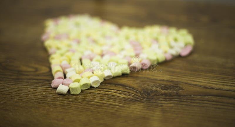 Sikt underifrån på hjärta som dras med marshmallower arkivfoton
