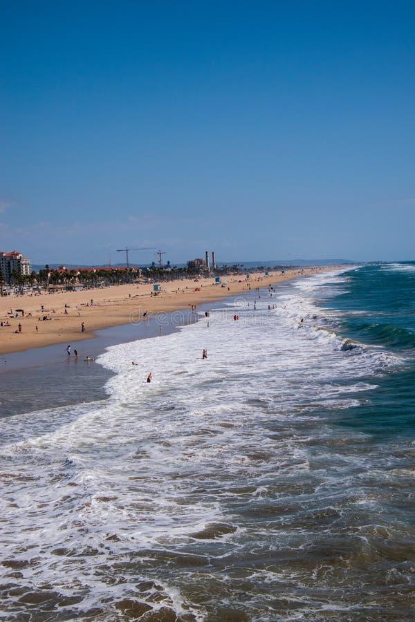 Sikt upp Huntington Beach med det grova havet med badare och surfare surrsikt arkivfoton