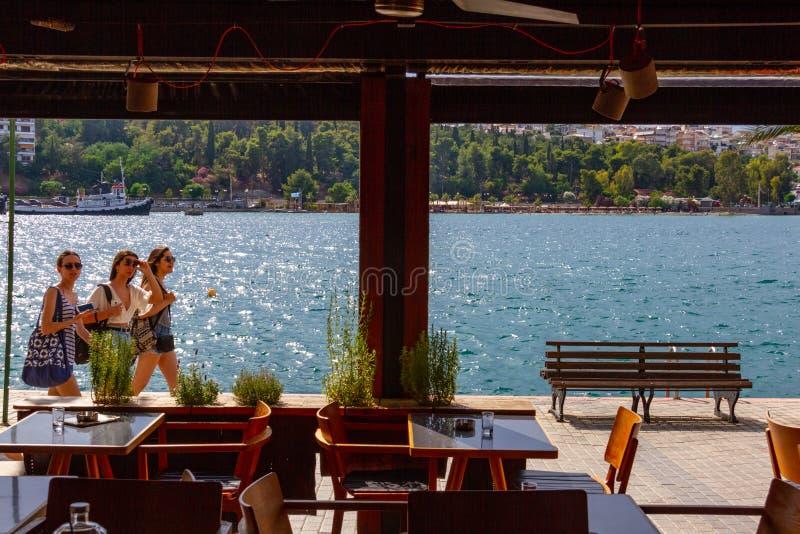 Sikt via kaféfönster av tre flickor som promenerar promenaden i chalcisen, Grekland royaltyfri bild
