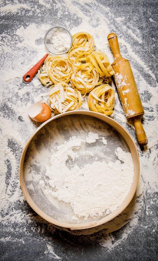 Sikta mjöl och pasta med en kavel och ägg På stentabellen Top beskådar royaltyfri bild