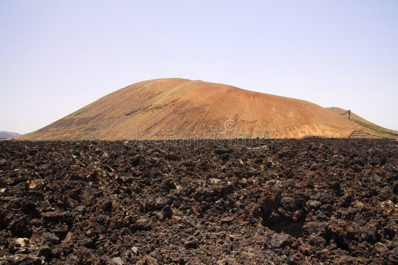 Sikten över fält av svart vulkanisk lava vaggar på röd kotte av berget - Timanfaya NP, Lanzarote arkivfoto