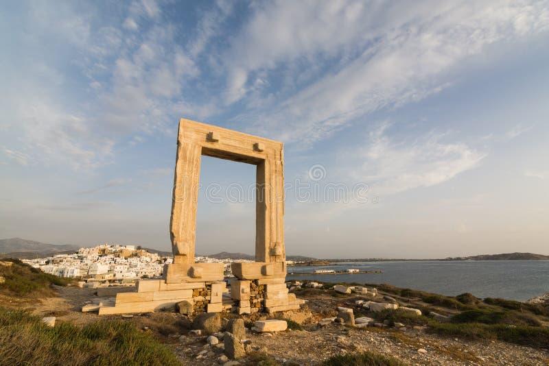Sikten över Naxos den gamla staden genom hela fördärvar av den forntida marmordörröppningsmonumentet Portara på solnedgången, Gre royaltyfri foto