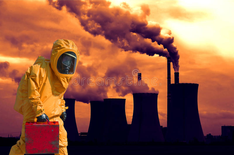Sikten av att röka kolkraftväxten på solnedgången och män i skyddande hazmat passar royaltyfri foto