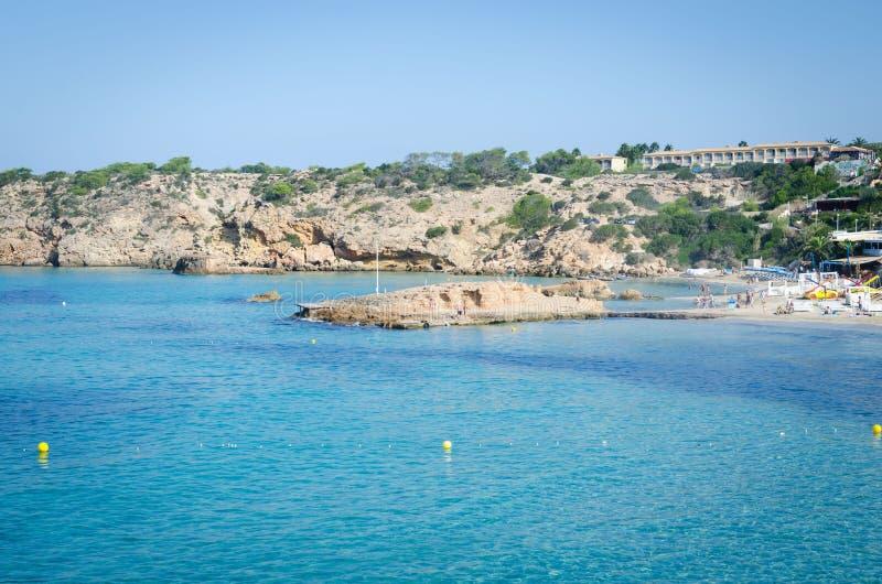 Sikten av Cala Tarida med vaggar i turkoshavsvatten, den Ibiza ön, Spanien royaltyfri bild