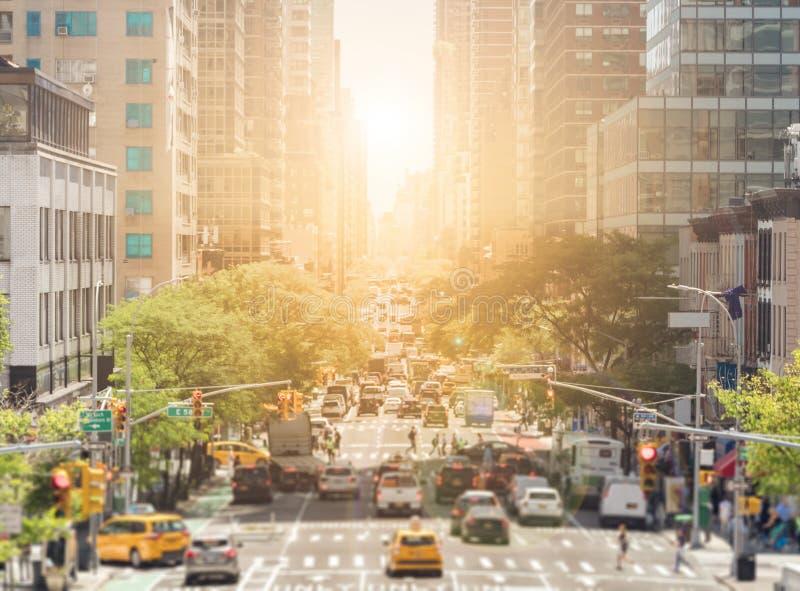 Sikten av den andra avenyn i New York City trängas ihop med bilar och folk i Manhattan med det ljusa ljuset av solnedgången i arkivbilder