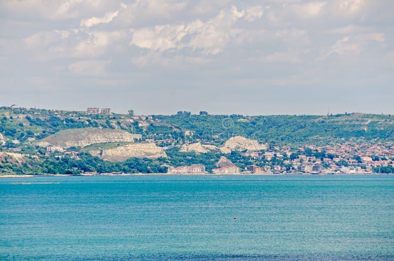 Sikten av den Black Sea kusten, gröna kullar med hus, blått fördunklar himmel StadsBalchik kust, blått havsvatten royaltyfria bilder