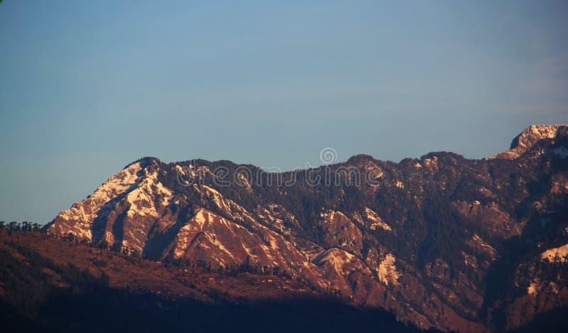 Sikten av den Manali staden och snö täckte Himalayan berg arkivfoton