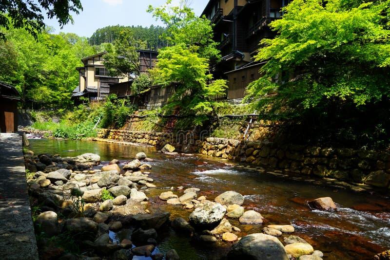 Sikten av den nya flodströmmen, stenbanken och naturliga vaggar stranden med gröna träd, och lokala byggnader i Kurokawa onsen st royaltyfri foto