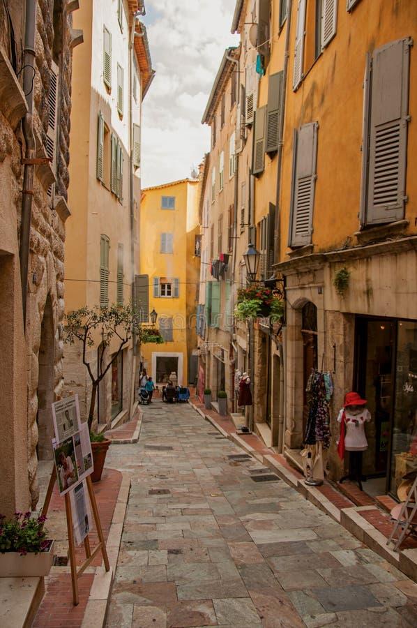 Sikten av den smala gatan och byggnader med shoppar i Grasse arkivfoton