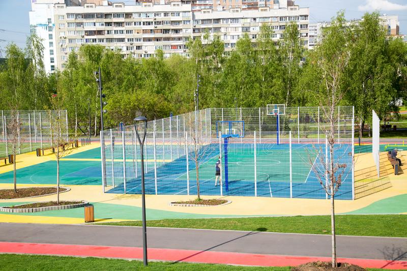 Sikten av denfärg sportjordningen i parkerar på bakgrunden av hus på en klar solig dag royaltyfria foton