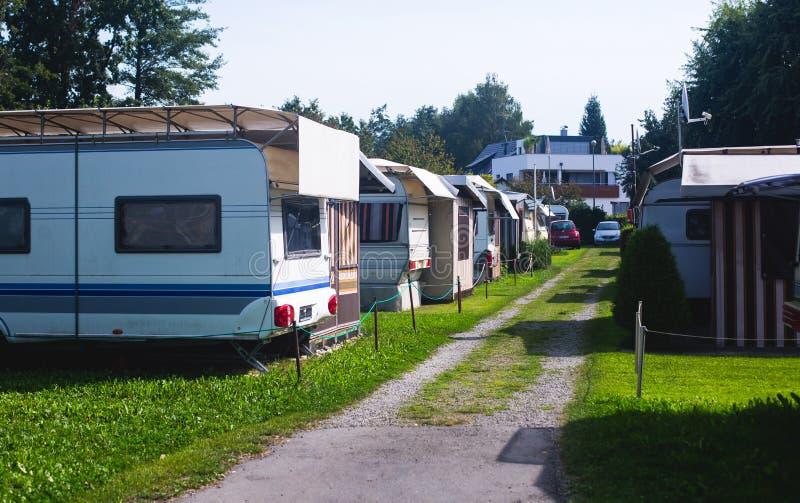 Sikten av det tyska campa stället med tält, husvagnar, släp parkerar och kabinstugahus royaltyfri bild