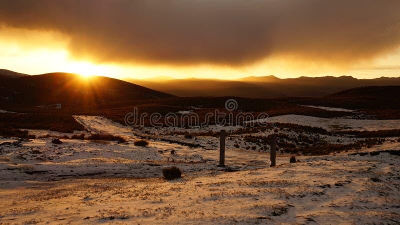 Sikten av en solnedgång i heden med snön täckte fältet med en molnig himmel arkivfoto