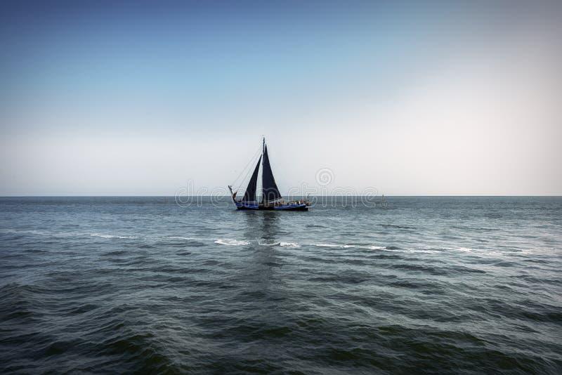 Sikten av ett ensamt segla skepp med svart seglar och att segla på de turbulenta pråm av en holländsk sjö fotografering för bildbyråer
