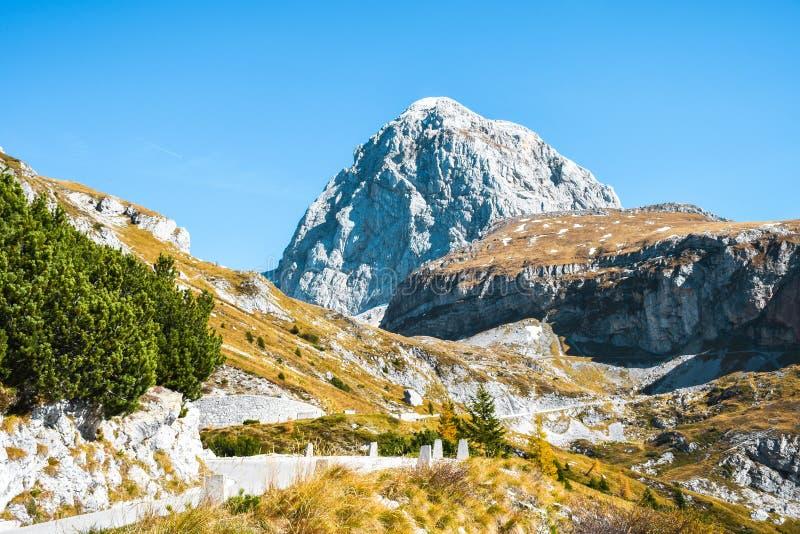 Sikten av ett härligt en gammal militär väg för det Mangart berget maximum och på en solig höst färgar dag arkivfoton