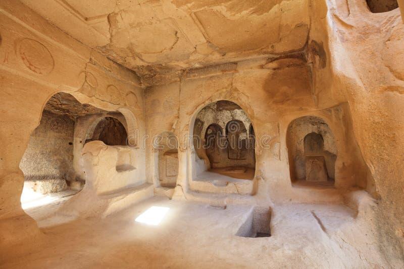 Sikten av fördärvar av lokalen av den forntida kyrkan i de gamla grottasandstenarna i dalarna av Cappadocia royaltyfri fotografi