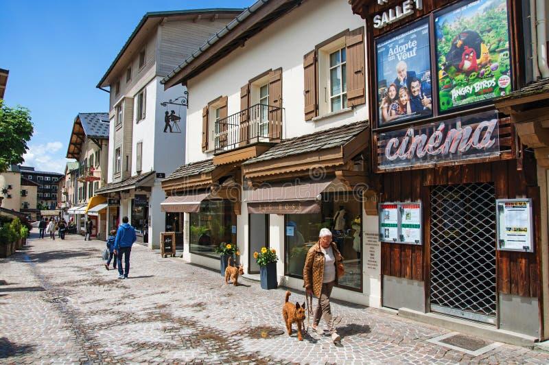 Sikten av gatan med shoppar, bion och översittaren med hunden i Megève arkivbilder