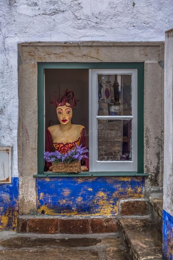 Sikten av gatan shoppar med en kuslig skyltdocka på fönster arkivfoto