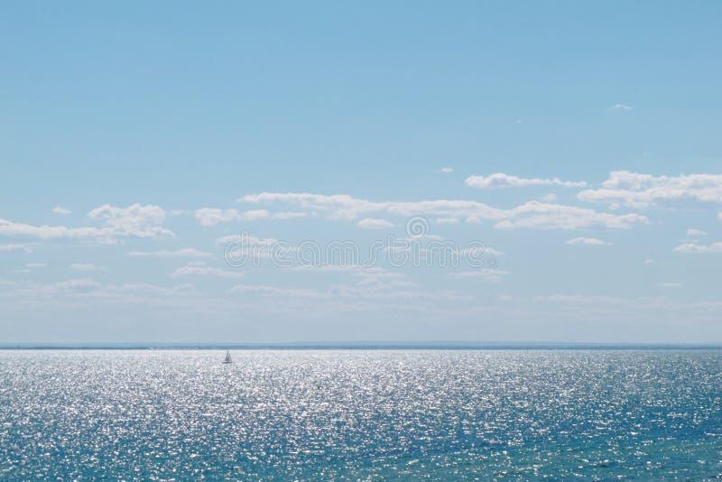 Sikten av gnistrandehavsvatten har segelbåten på blå himmel på den Sandringham stranden arkivbilder