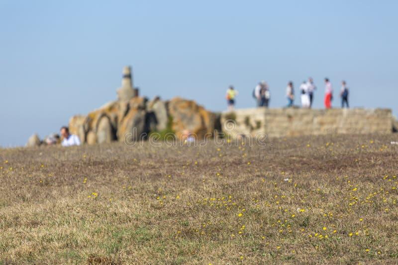 Sikten av grästextur i perspektivet, bakgrundssuddighet med vaggar och folk, nära havet royaltyfria foton