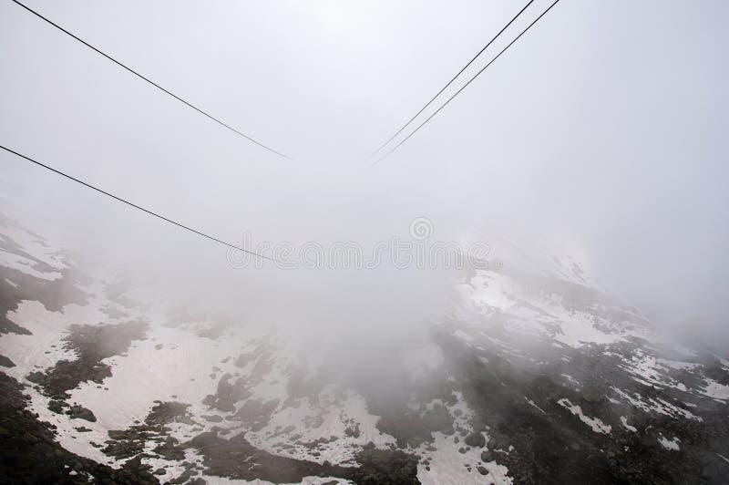 Sikten av kabelbilen kablar på vägen upp till Aiguille du Midi i franska fjällängar royaltyfria foton