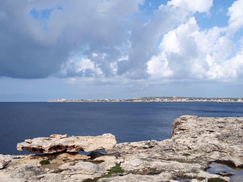 Sikten av kusten och steniga klippor uthärdar ciutallamenorca med ljus reflekterade på ett lugna blått hav och semesterortbyggnad arkivfoton