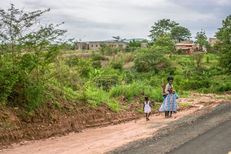 Sikten av kvinnan med barn promenerar vägrenen, typisk afrikansk by som bakgrund arkivbild