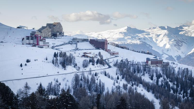 Sikten av La Plagne Aime 2000 skidar semesterorten i franska savojkålfjällängar Snö täckte berg och byggnader royaltyfri bild