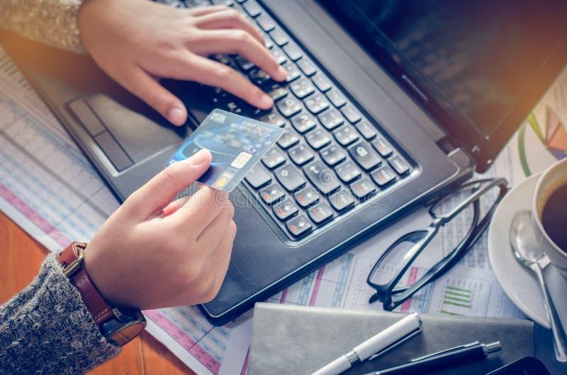 Sikten av mannen räcker hållande kreditkortnummer som skrivas på datortangentbordet, medan sitta på ett skrivbord - fokusera hand royaltyfri bild