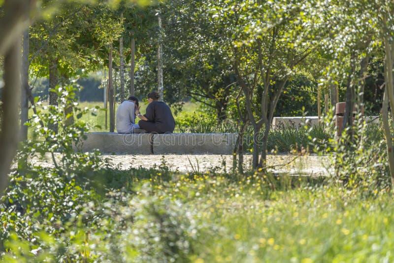 Sikten av modern som talar till hennes son, som gråter som sitter på en stenbänk, i staden, parkerar royaltyfria bilder