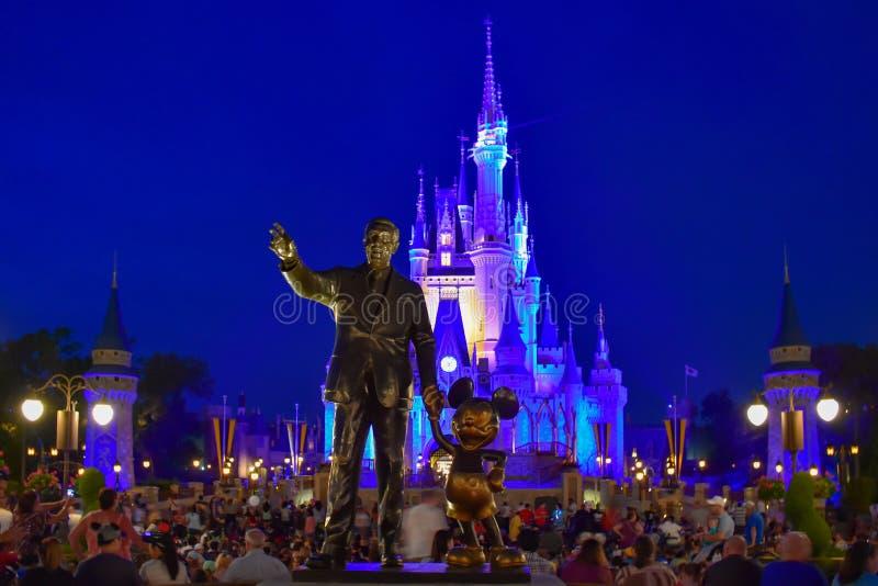 Sikten av partnerstatyn denna staty av Walt Disney och Mickey Mouse placeras framme av upplysta Cinderella Castle i mor fotografering för bildbyråer