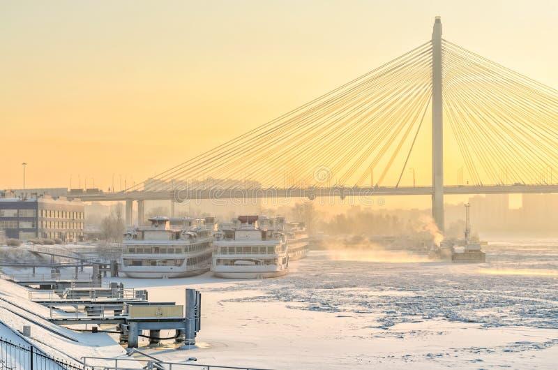 Sikten av passagerareporten och den Bolshoy Obukhovsky bron på en frostig disig vinterdag royaltyfri bild