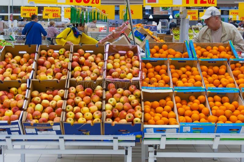 Sikten av rader av lådor boxas med äpplen och apelsiner i supermarketledare royaltyfri foto