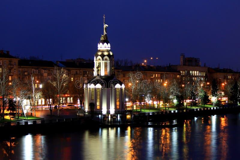 Sikten av staden Dnepr, Ukraina, kyrka med exponering på höstaftonen, ljus reflekterade i vattnet royaltyfria foton