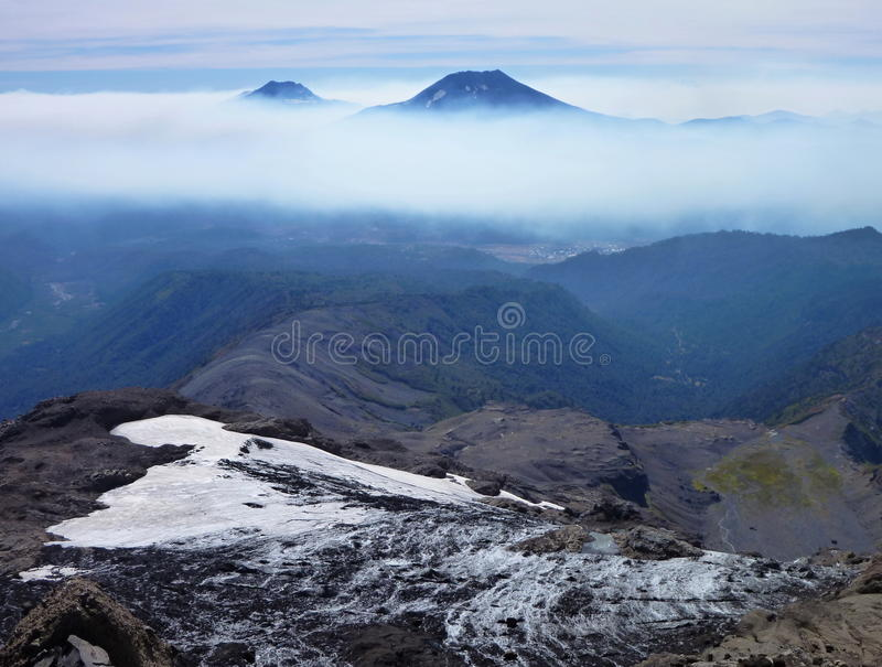 Sikten av tolhuacaen och den lonquimay vulkan når en höjdpunkt från toppiga bergskedjan nevada i chile arkivfoton