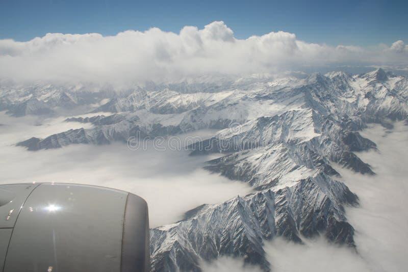 Sikten av turbinmotorn och snö täckte berg från flygplanfönster arkivfoton