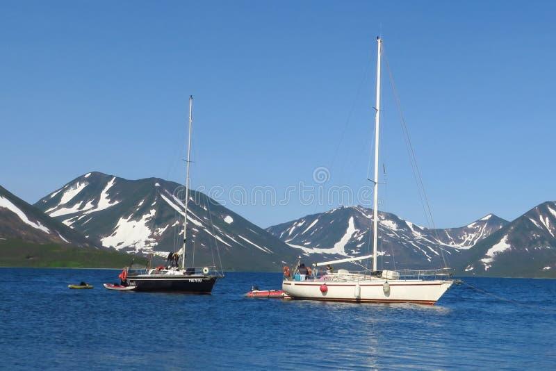 Sikten av två yachter under det vitt och svart seglar konkurrerar i lagseglinghändelse Nordsjö, blå himmel och berg som royaltyfri fotografi