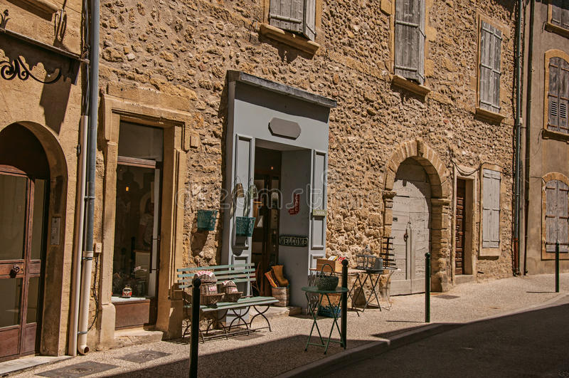 Sikten av typiska stenhus och shoppar på en gata av Lourmarin royaltyfri foto