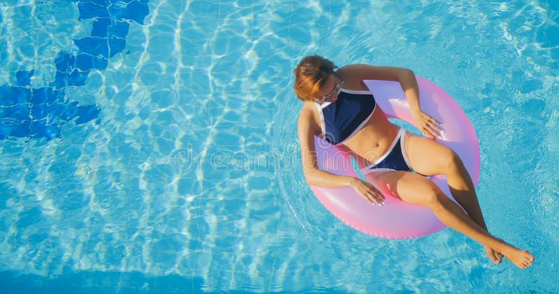 Sikten av ung brunettkvinnasimning på de uppblåsbara rosa färgerna ringer royaltyfri fotografi