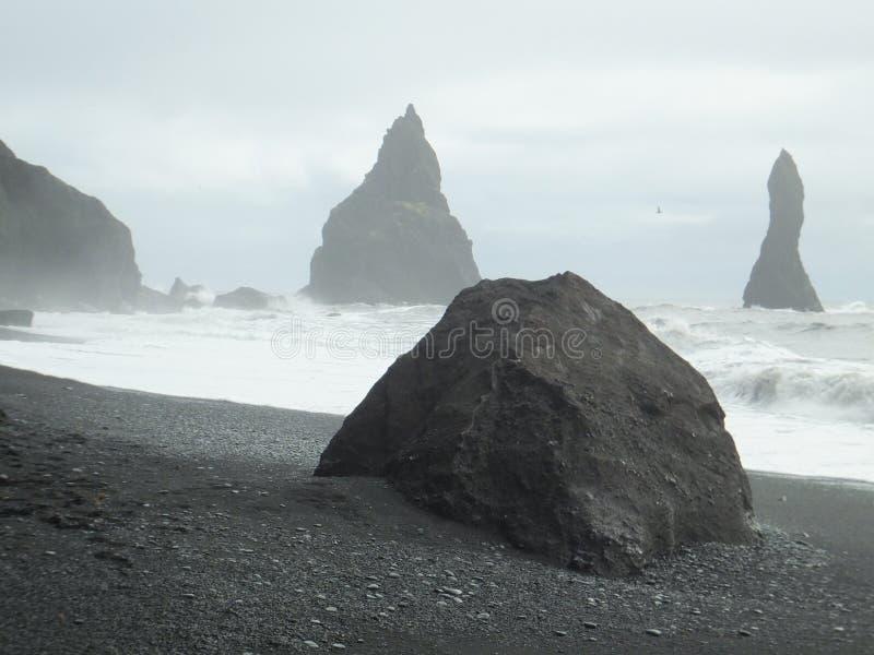 Sikten av vaggar bildande i havet av den Reynisfjara svartstranden på den Iceland's sydkusten royaltyfri fotografi