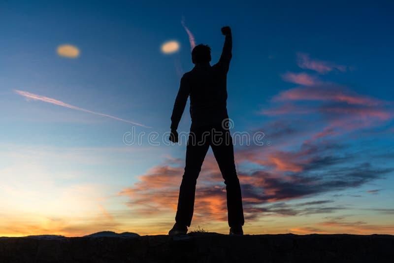 Sikten bakifrån av en man som står överst av en vägg med hans arm, lyftte högt arkivbilder