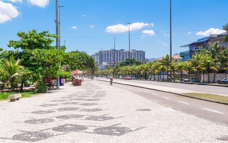 Sikten Barra da Tijuca med gömma i handflatan och mosaiken av trottoaren i Rio de Janeiro arkivbilder