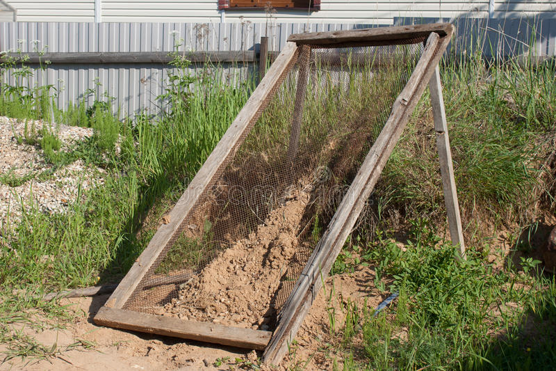Sikten för att torka och att sålla sand arkivfoton