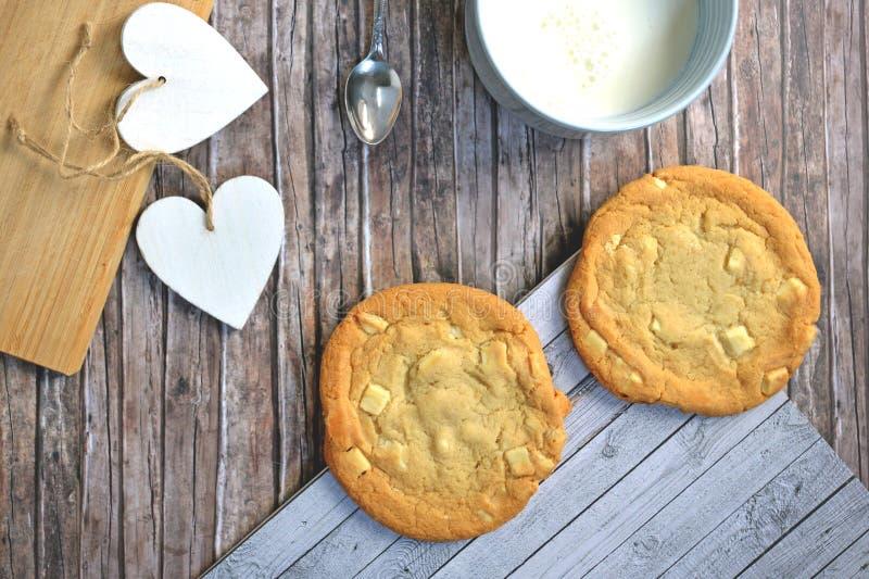 Sikten för den höga vinkeln av vita kakor för chokladchiper med koppen av mjölkar och skedar på träbakgrund royaltyfri foto