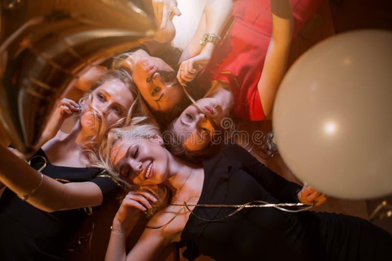 Sikten för den låga vinkeln av fyra härliga Caucasian kvinnor som bedrar framställning omkring, fejkar mustaschen från deras eget arkivfoto